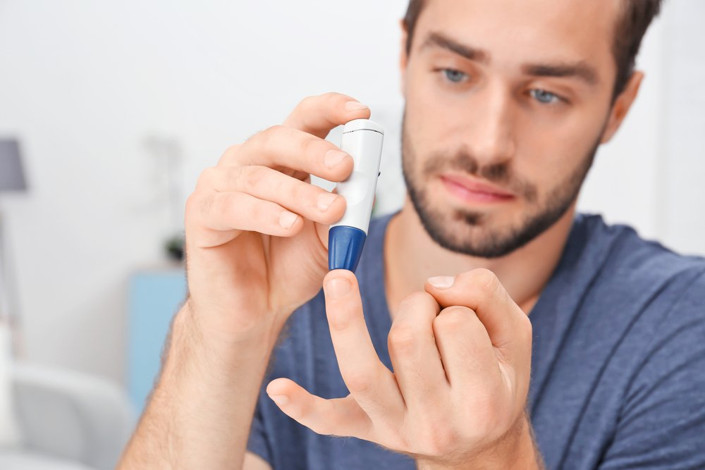 a man checking his blood sugar levels with device