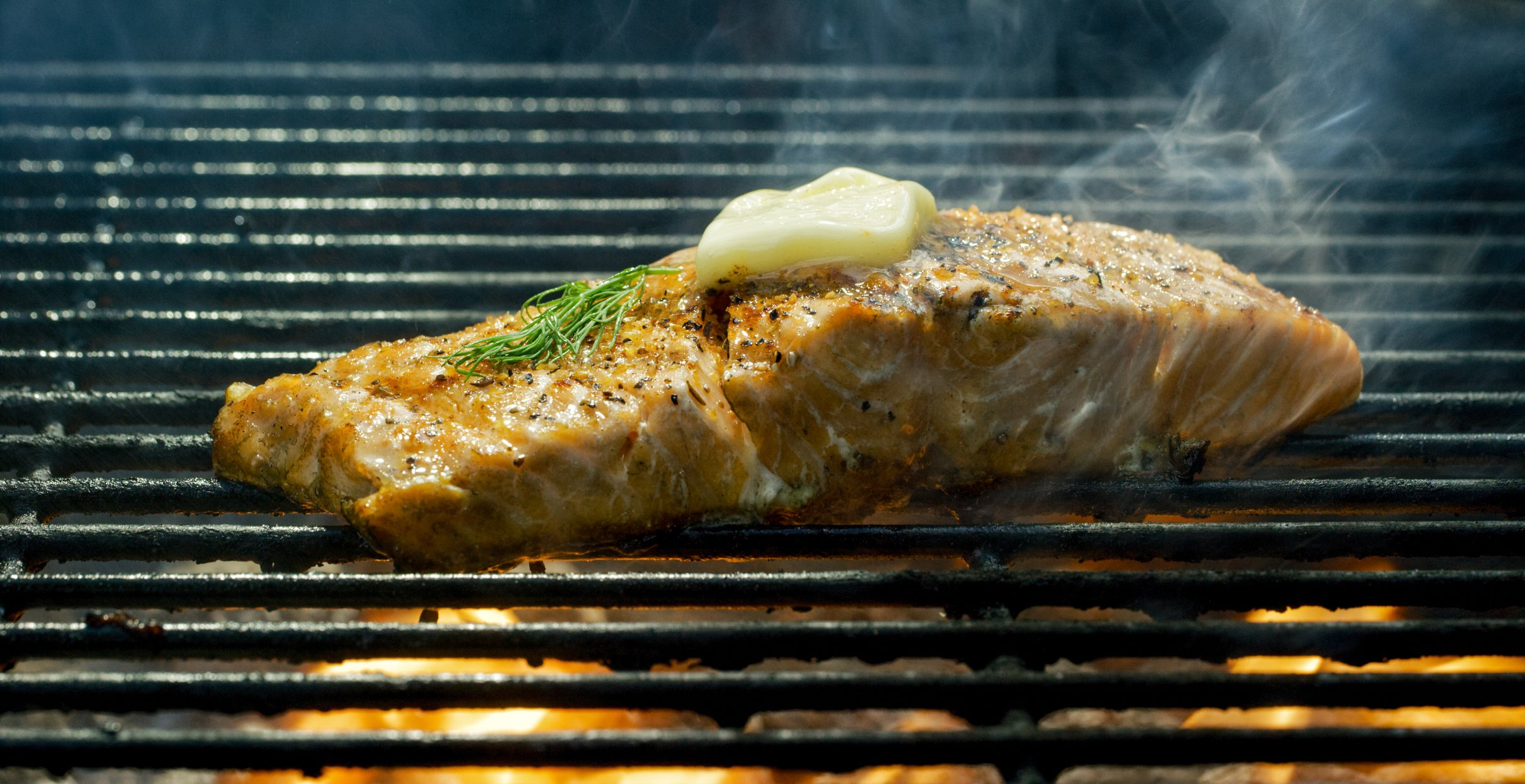 A Seasoned Salmon Steak Fillet Cooks on a Flaming Barbecue Grill