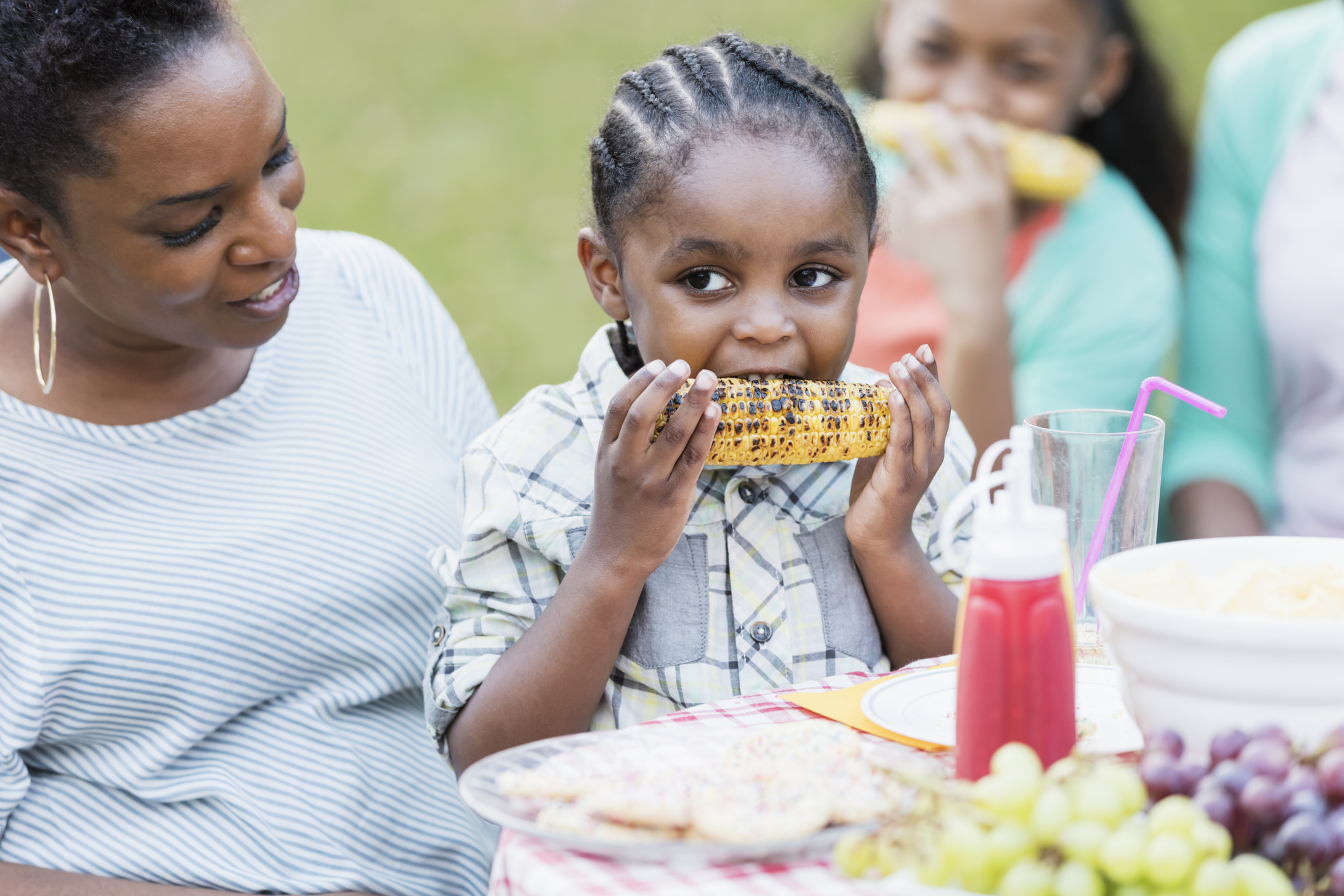 A little 3 year old African-American boy sitting on his mother's lap at a backyard cookout, eating corn on the cob.