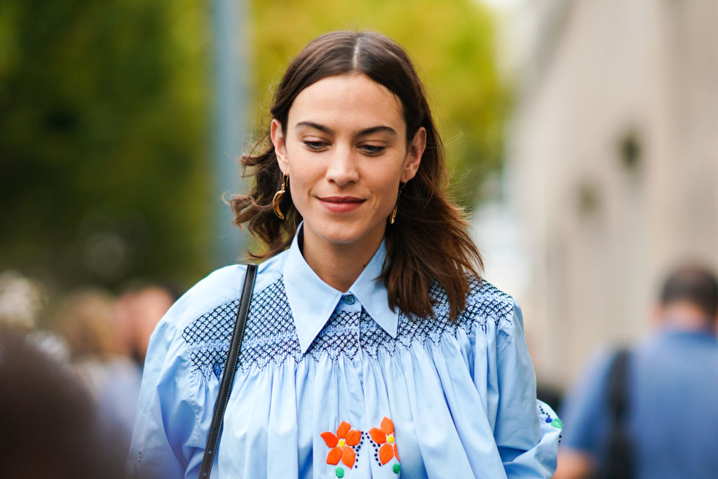 MILAN, ITALY - SEPTEMBER 18: Alexa Chung wears a blue pleated shirt with floral embroidery, earrings, outside the Prada show during Milan Fashion Week Spring/Summer 2020 on September 18, 2019 in Milan, Italy.