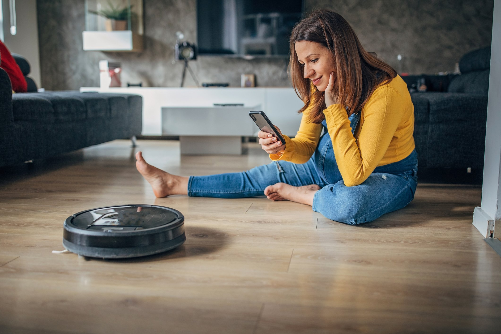 Pregnant woman using phone while robot vacuum cleaner is cleaning her home.