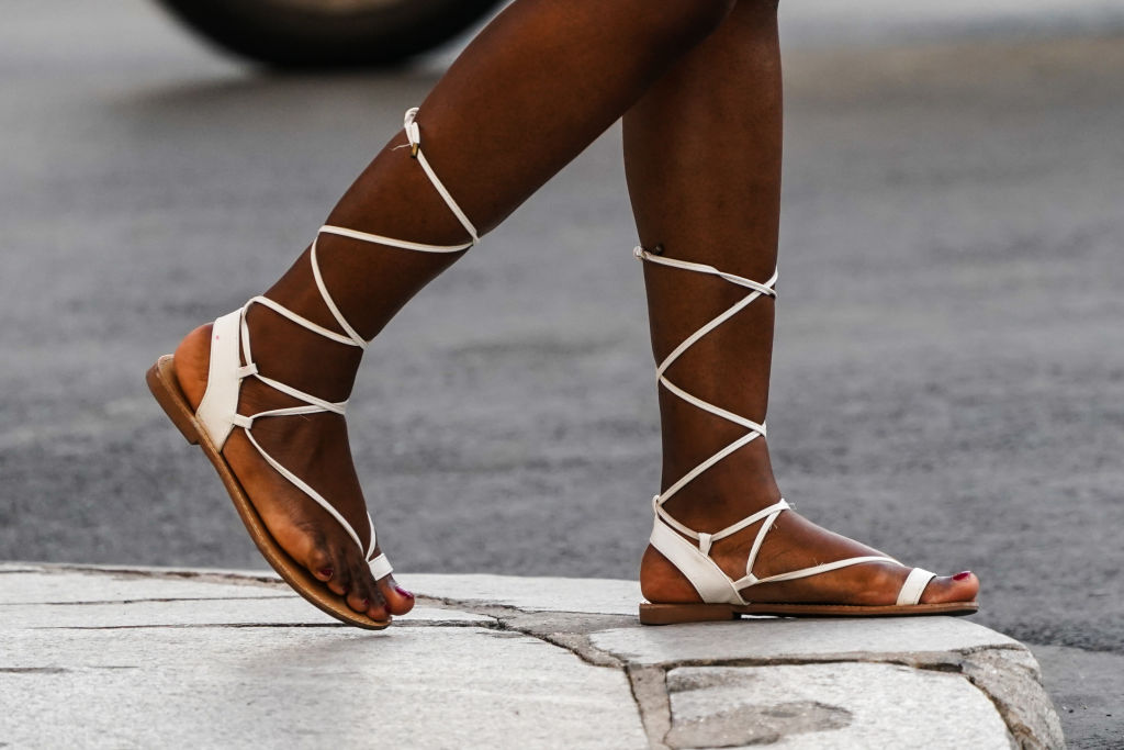 A passerby wears white lace-up flat shoes, on June 25, 2020 in Paris, France.