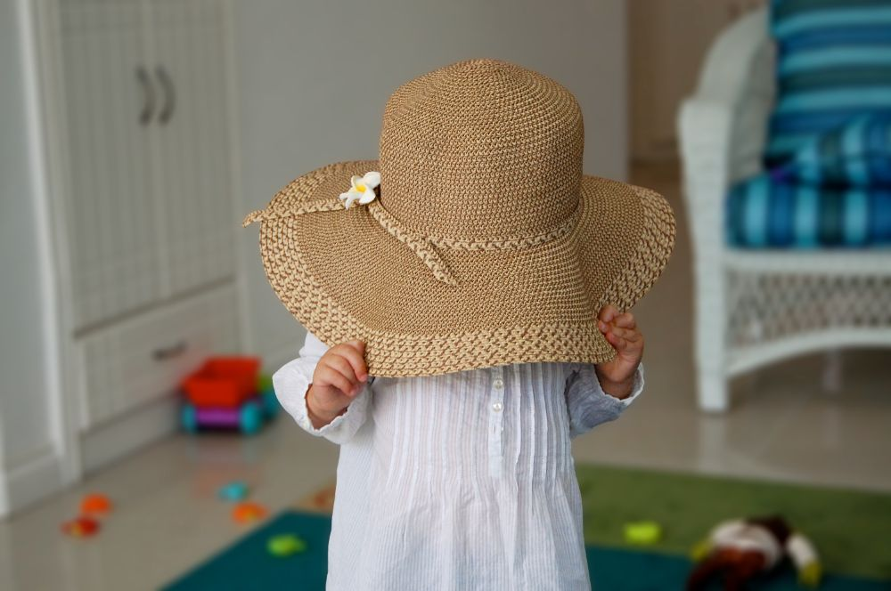 one year old baby playing hide and seek with a hat