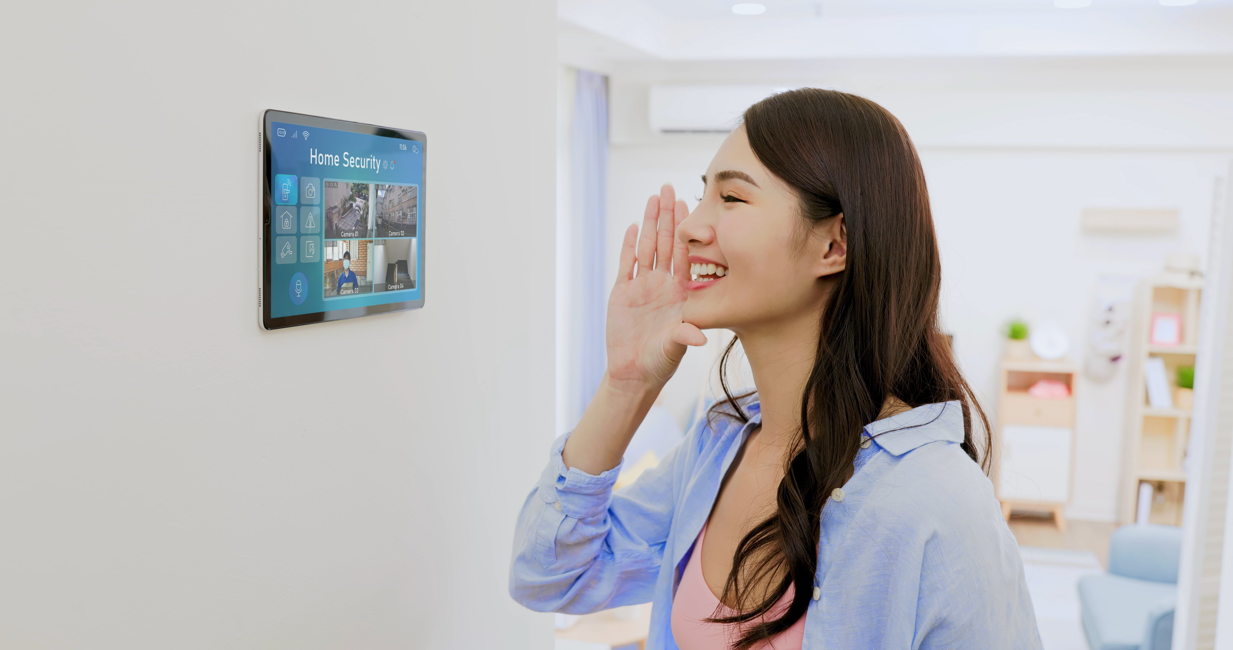Smiling Asian woman looking at home security camera On Digital Tablet of wall - talking to the delivery man standing outdoor holding a package