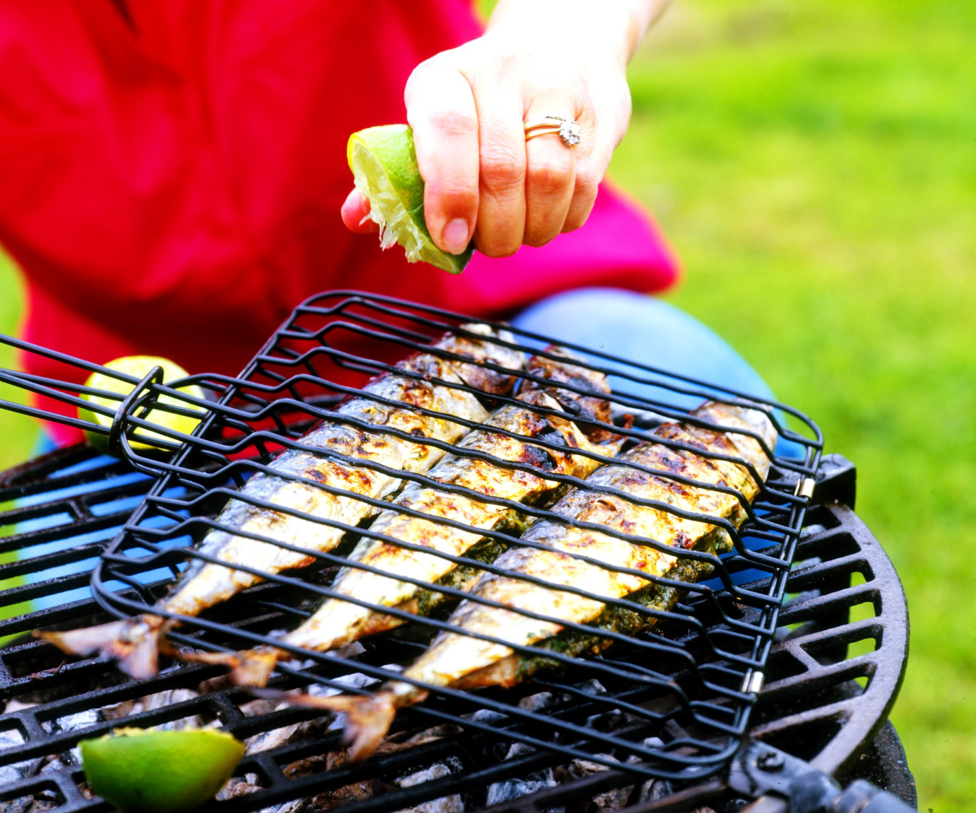 Lime being squeezed over mackerel on barbecue