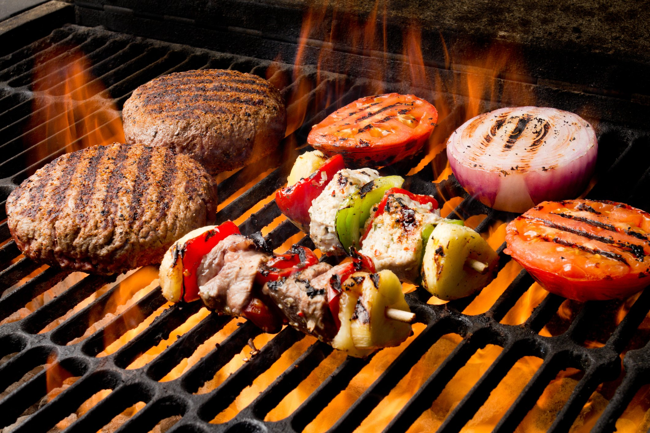 Chicken Shish Kebabs with bell pepper and grilled chicken breast and beef Grilled Burger, Tomato, Onion on a flaming old fashioned charcoal barbecue grill with perfect grill marks on everything