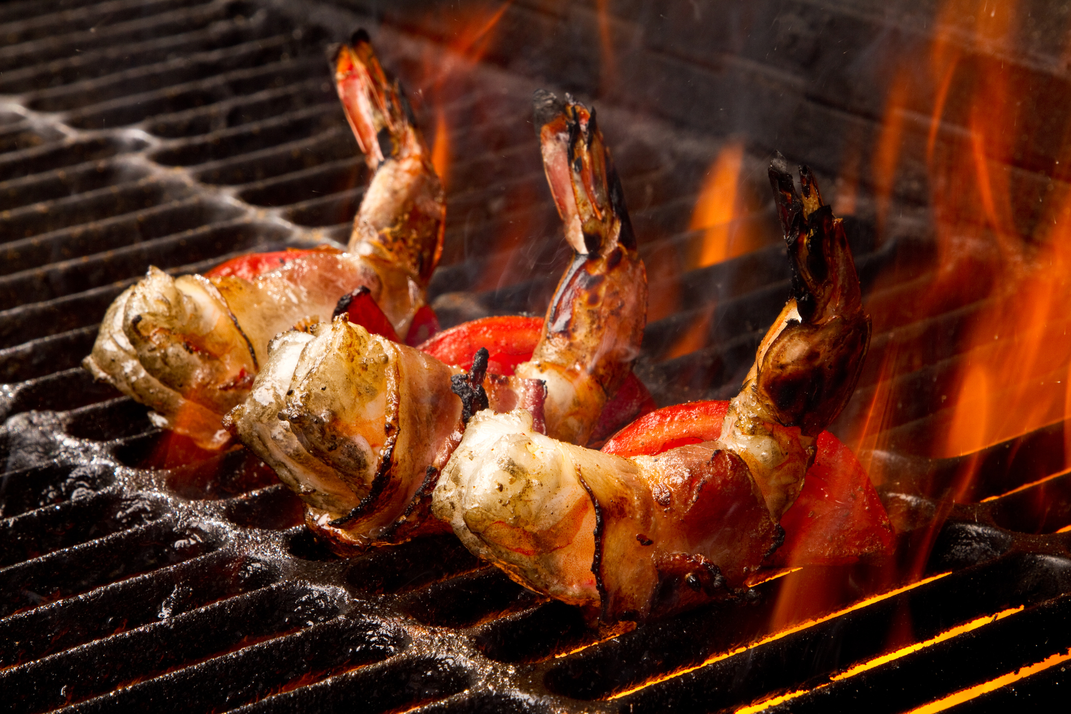 Row of three succulent jumbo shrimp or prawns wrapped in bacon on an old fashioned charcoal grill with flames leaping up to sear them. Cooking is bringing out a golden brown and red color on the shrimp.