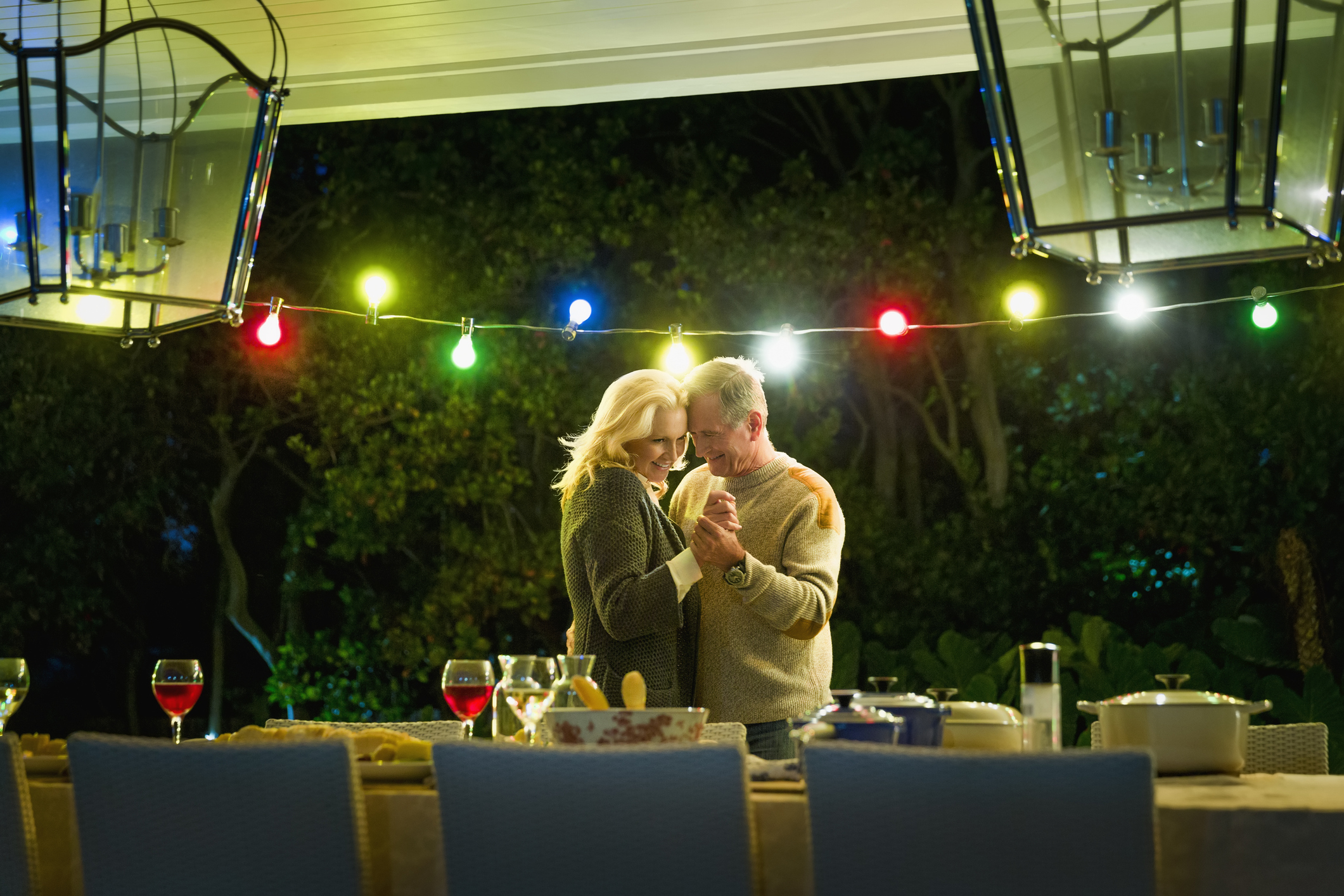 Romantic senior couple dancing at table on illuminated porch