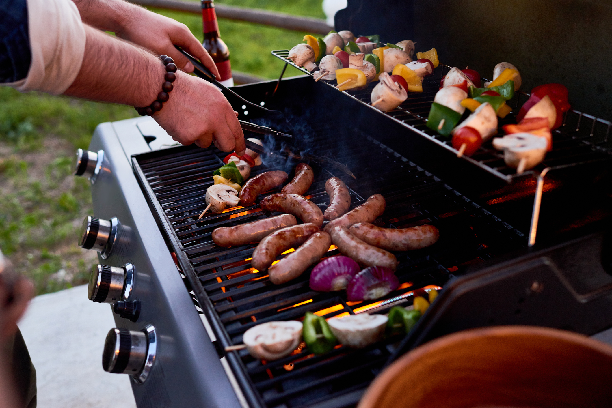 Chef cooking sausages and vegetables on skewers outdoors