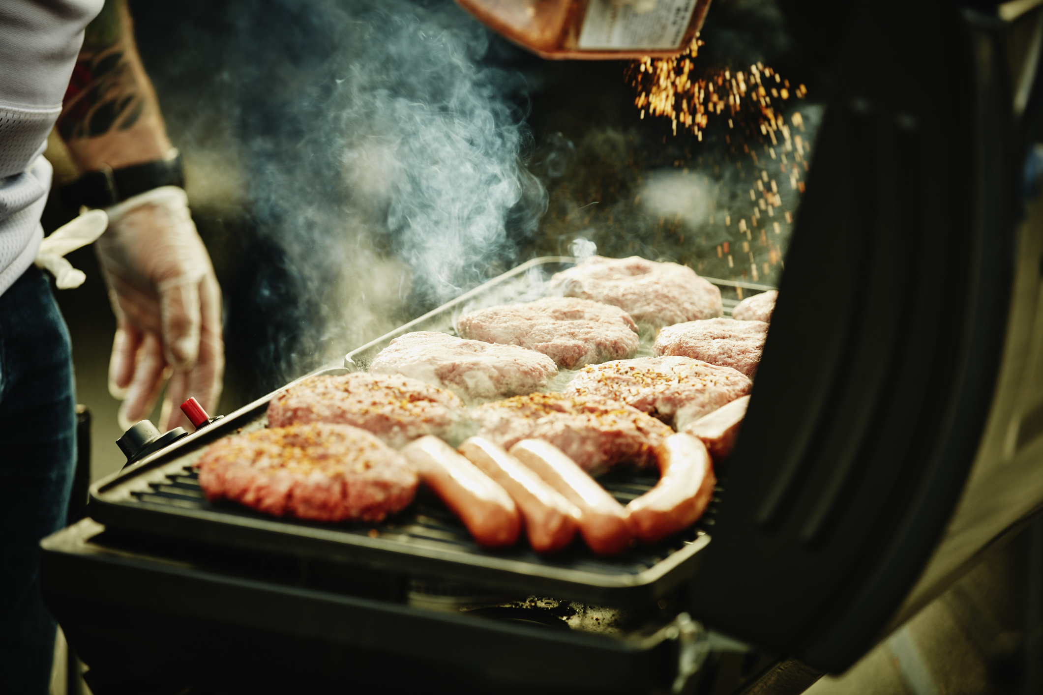 Man seasoning burgers and hot dogs on barbecue during tailgating party