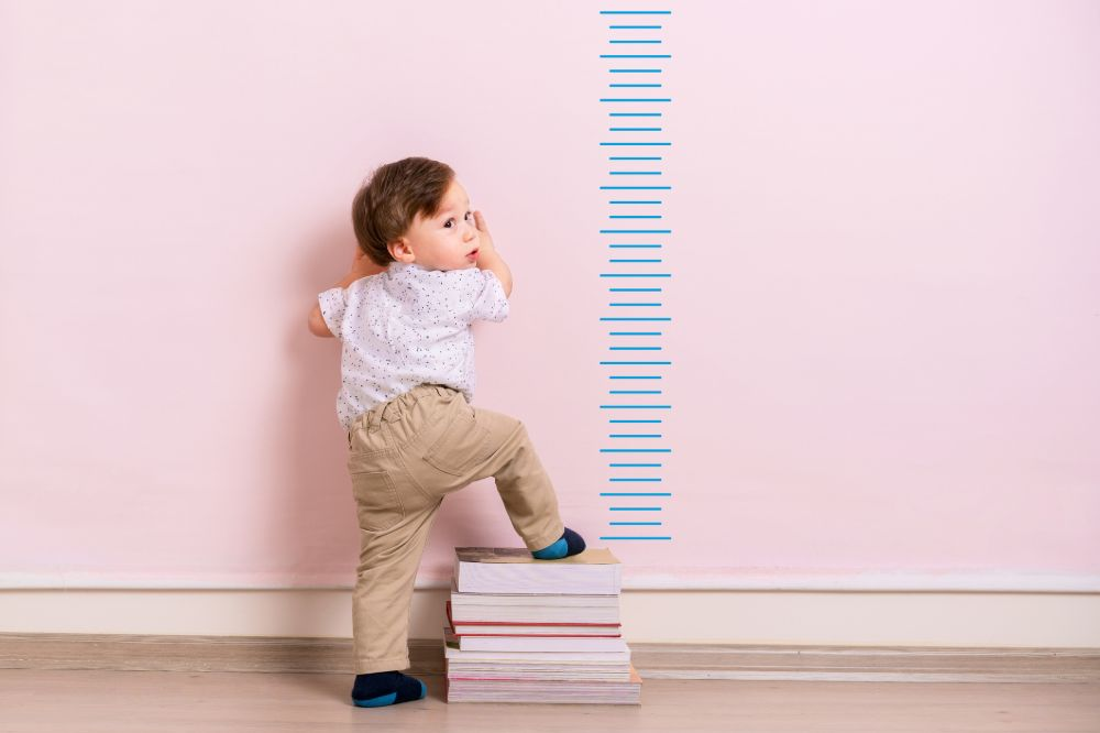 one year old boy climbing on books beside height chart