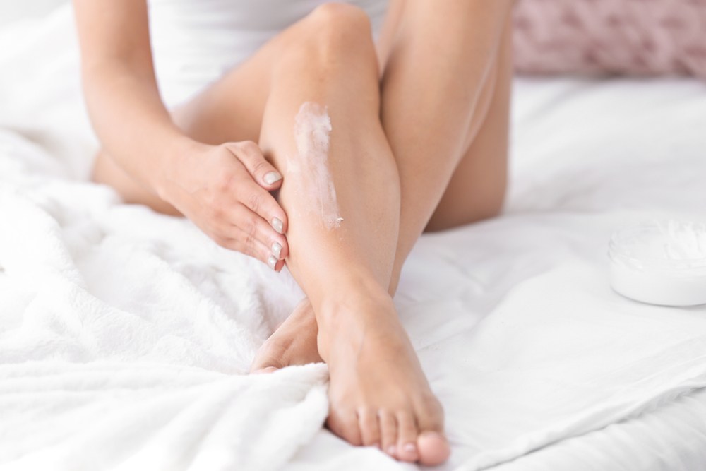 woman applying lotion to her lower leg