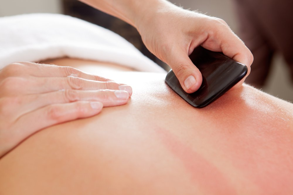 massage therapist using gua sha tool on client's back
