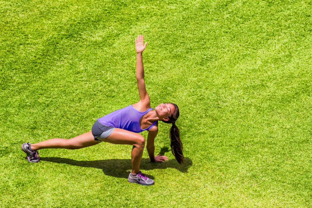 drone image of woman doing twisted lunge stretch