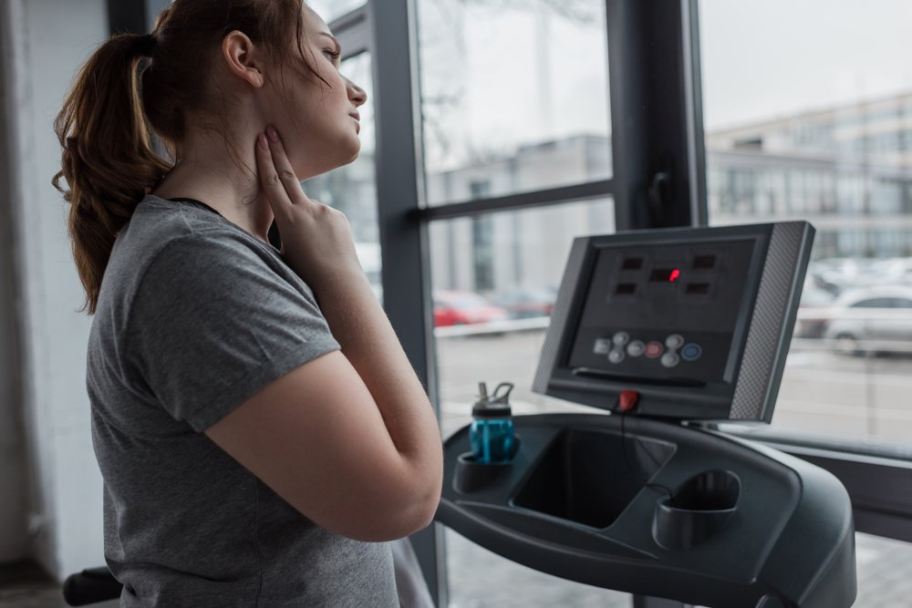 young woman on treadmill taking her pulse