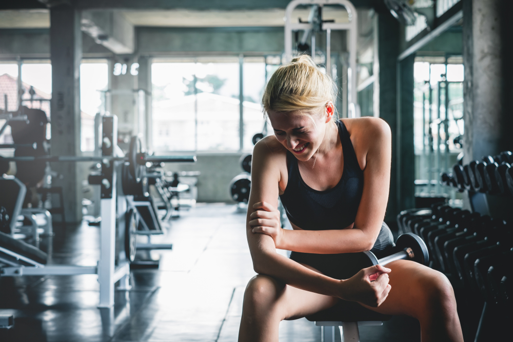 woman in gym experiencing lactic acid buildup in arm muscle
