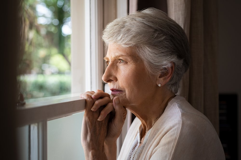 older woman looking serious out of window