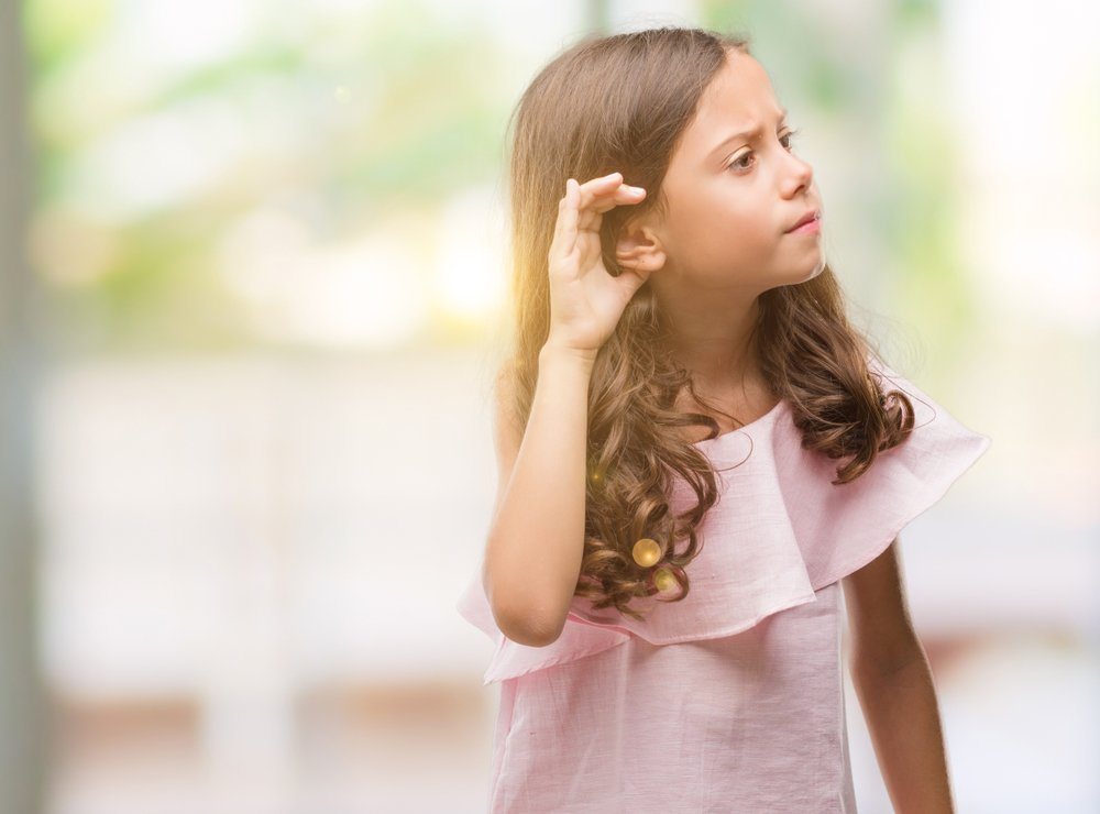 little girl with her hand cupped to her ear