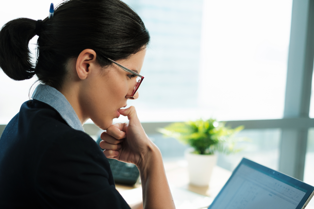 woman biting her thumb nail while focusing on work