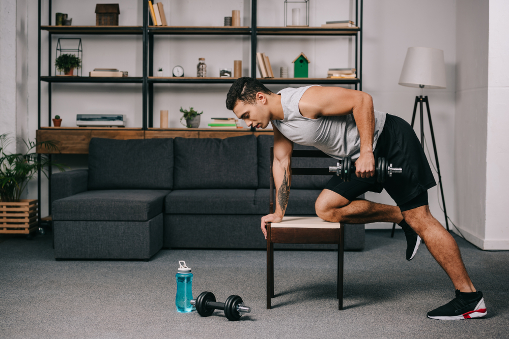 fit man in his living room lifting weights
