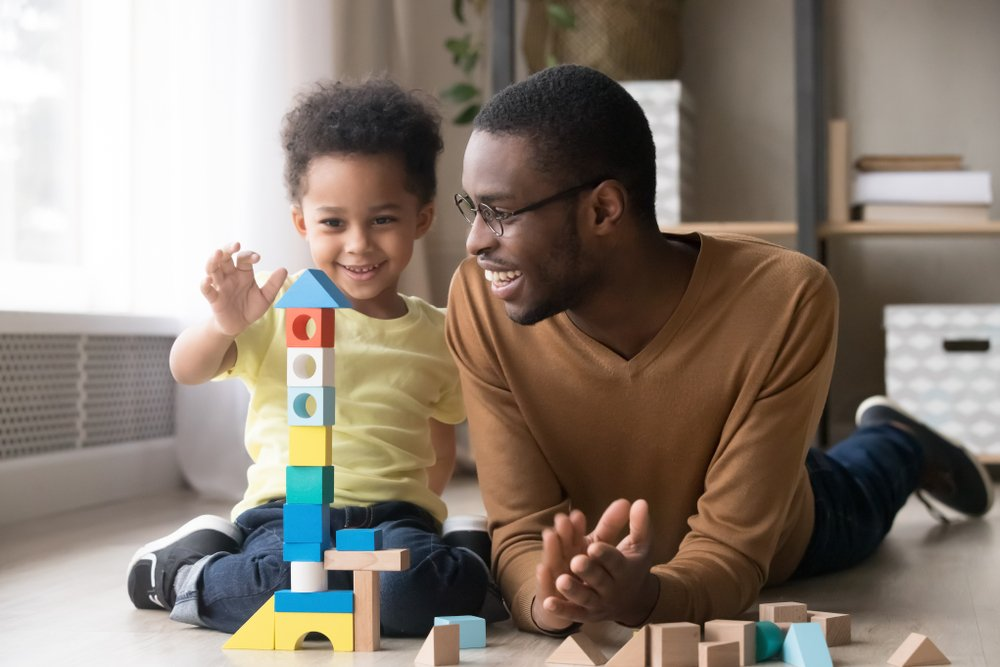 father and young son playing with blocks
