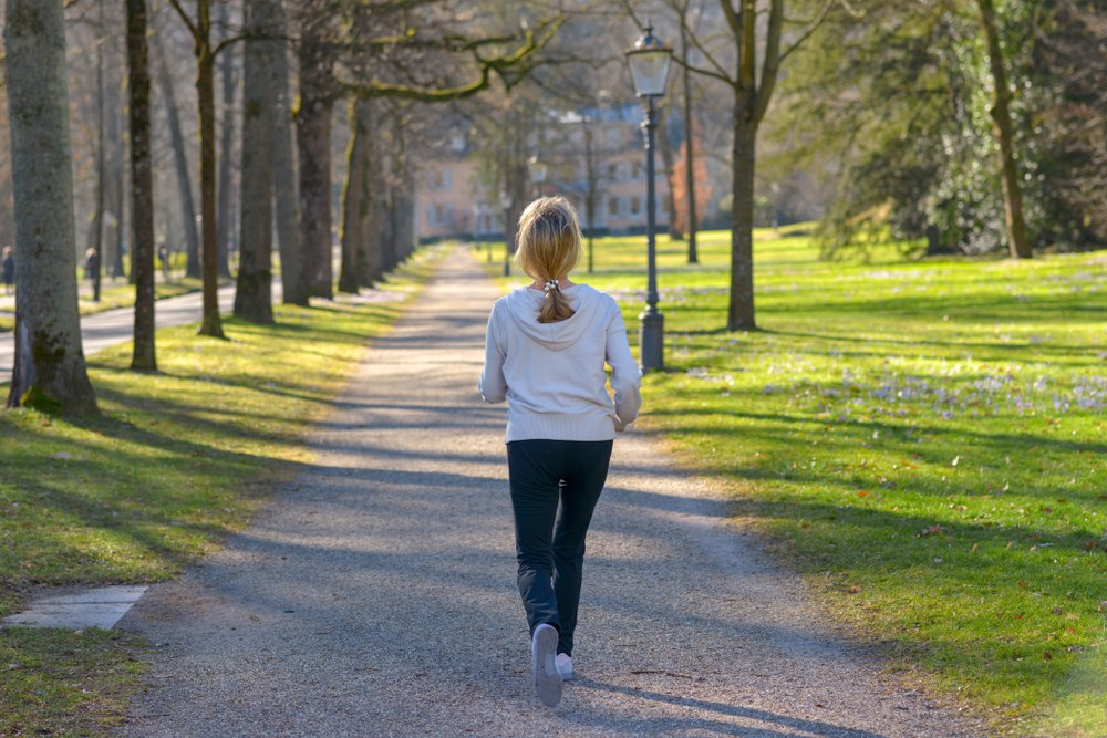 middle aged woman speed walking through park