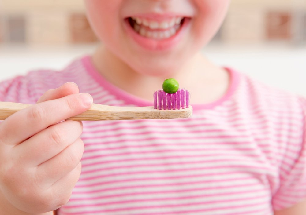 little girl holding up a toothbrush with a pea on it