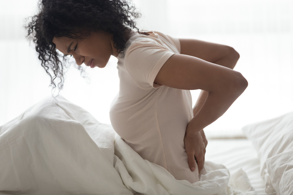 woman waking up in bed with back soreness
