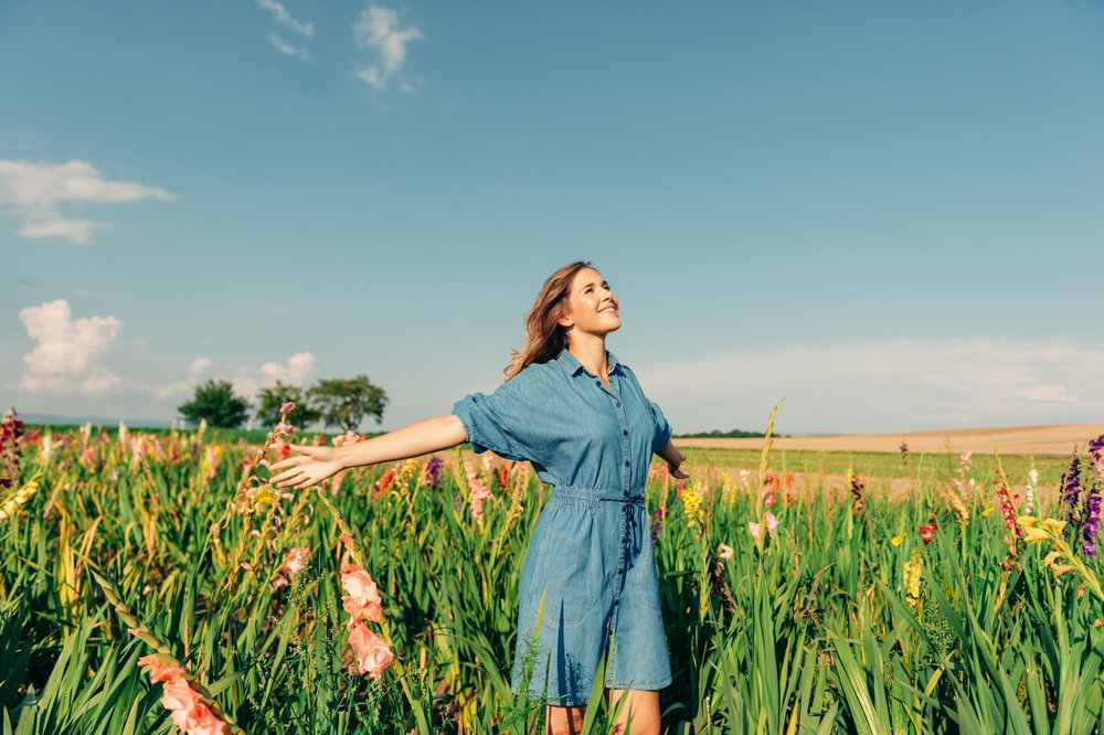 Outdoor portrait of pretty young girl in countryside, wearing denim dress, arms wide open