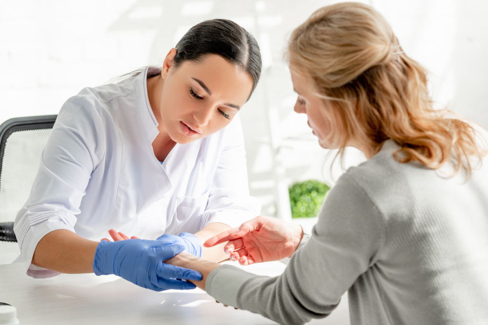 dermatologist examining patient's forearm