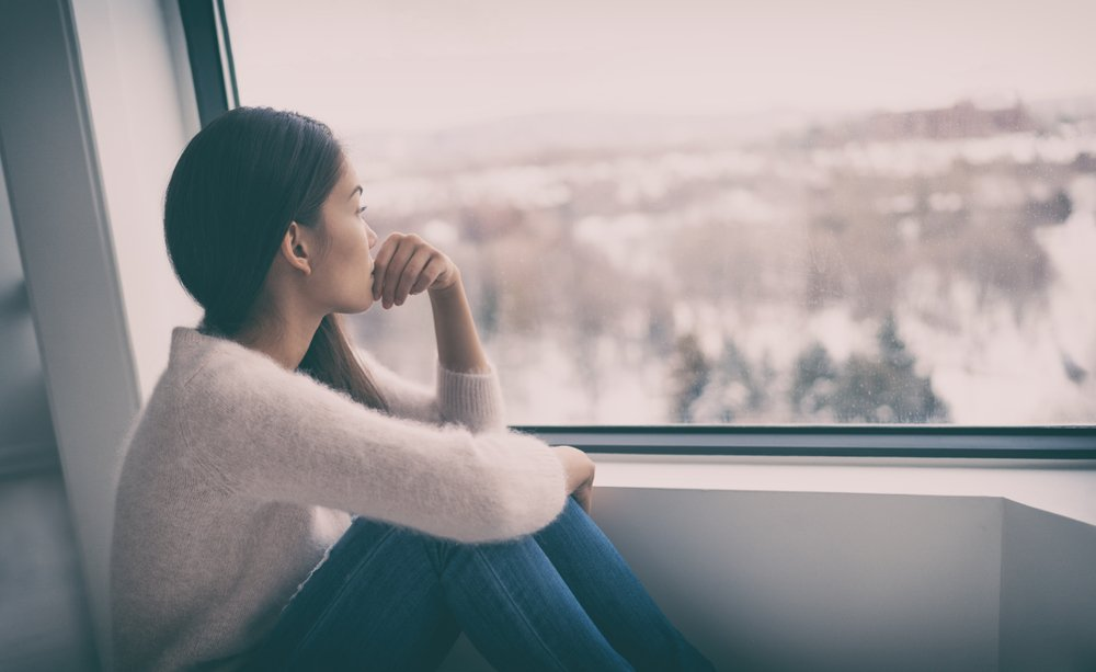 young depressed woman looking out window, biting nail