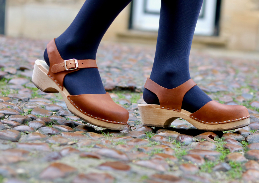 A close up of a woman's legs walking with beautiful leather and wood clog shoes on a cobblestone cobble street