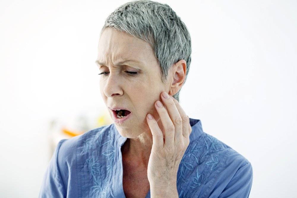 older woman experiencing jaw pain or lockjaw