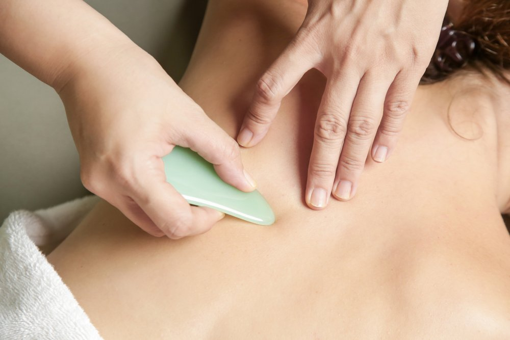 practitioner using gua sha tool on patient's back
