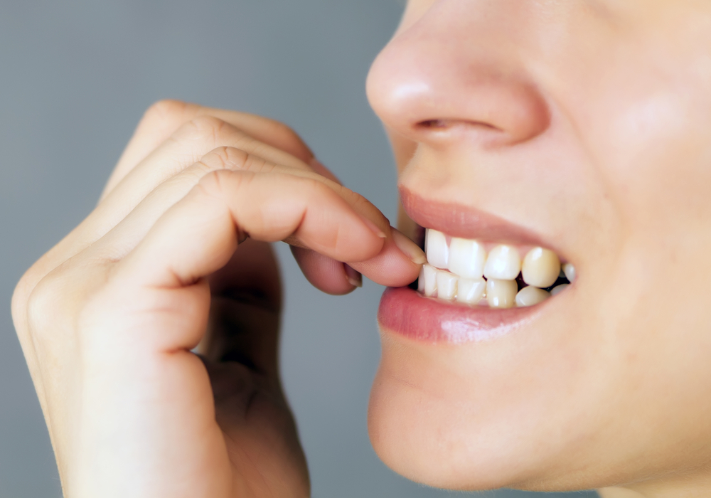 cropped image of a woman chewing her fingernails