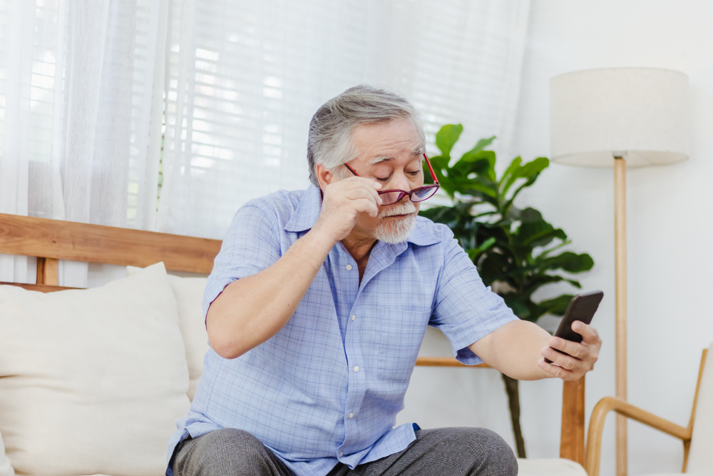 man removing glasses to see his phone because of blurry vision