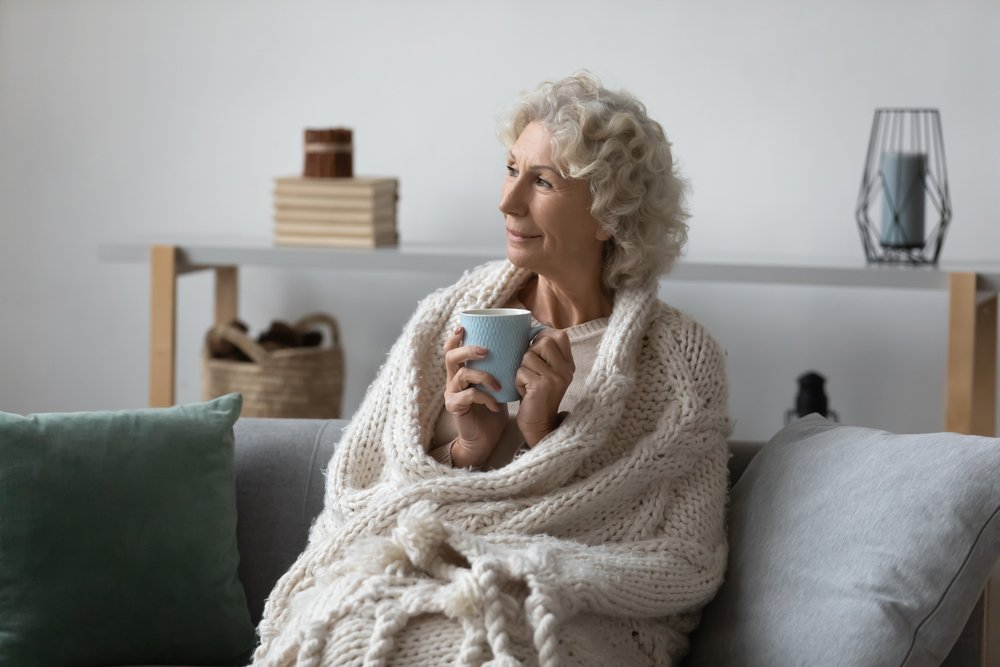 older woman with blanket and tea smiling into the distance