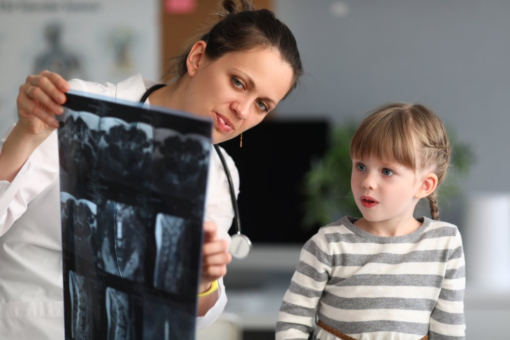 pediatric specialist showing little girl patient her MRI results