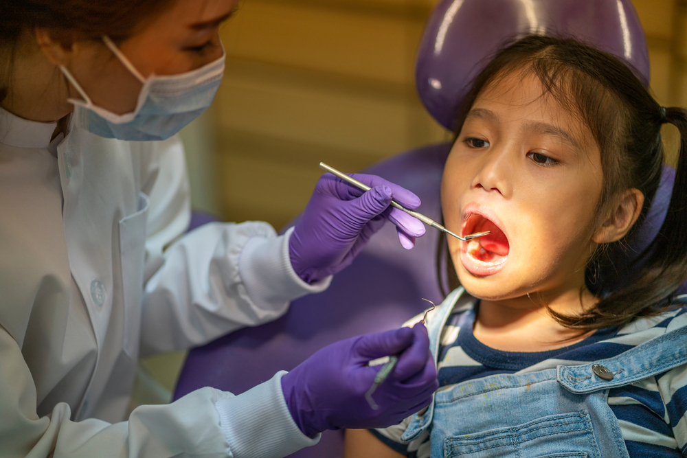 dentist checking young patient's teeth