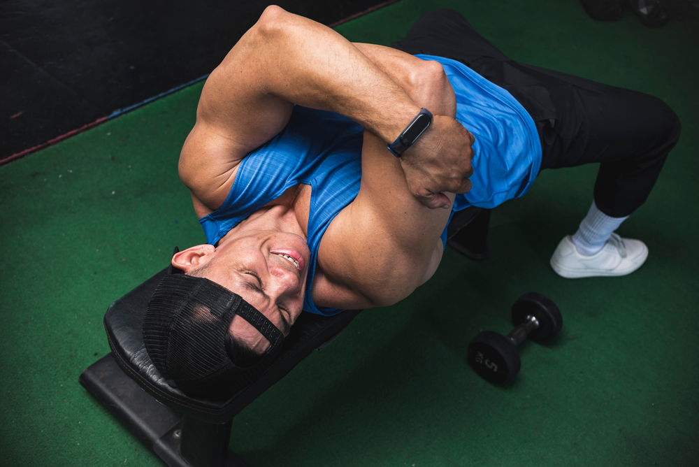 man at gym feeling pain in tricep during workout