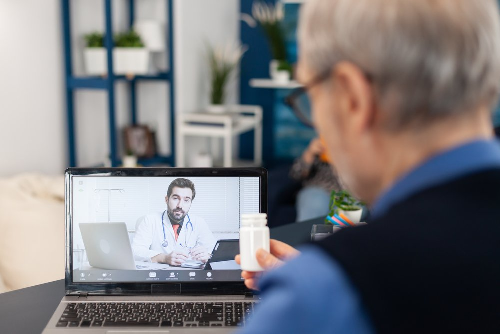 older man speaking with doctor virtually, holding pills