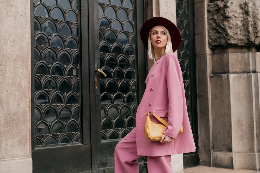 elegant woman wearing trendy pink suit, burgundy color hat, holding yellow bag, posing in street of city