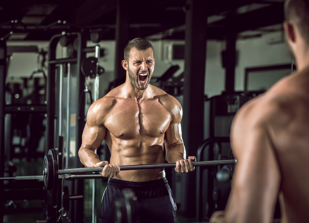 man feeling pain while lifting barbell weights