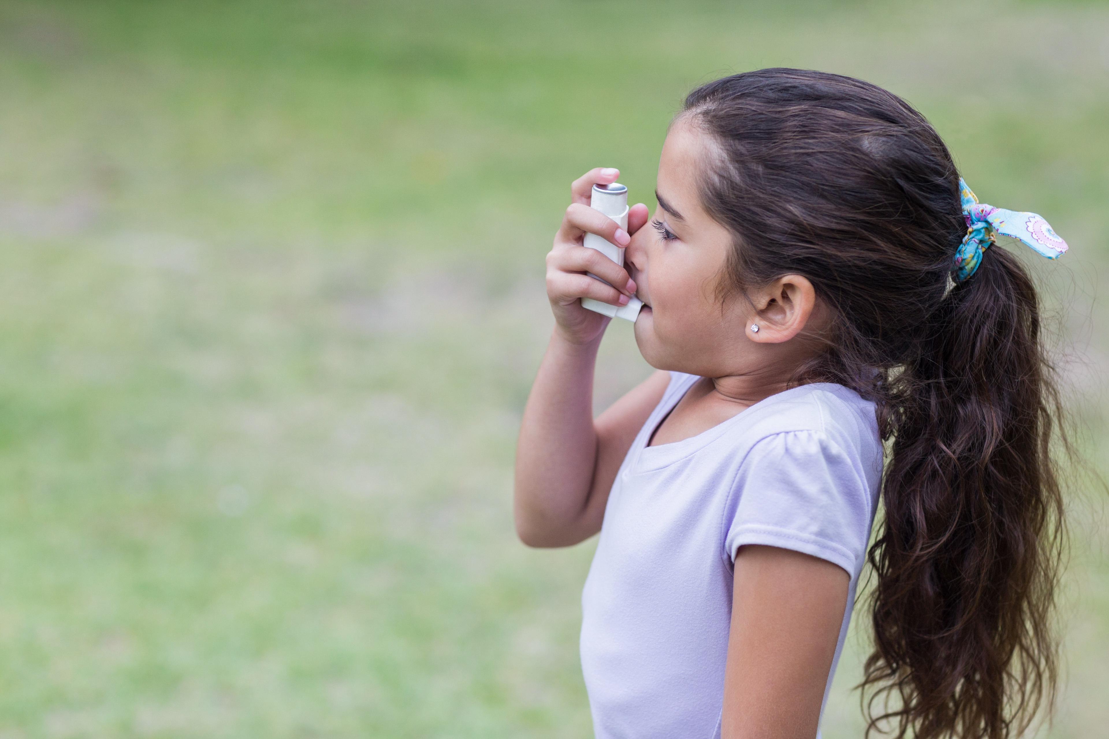 little girl outdoors using her asthma inhaler