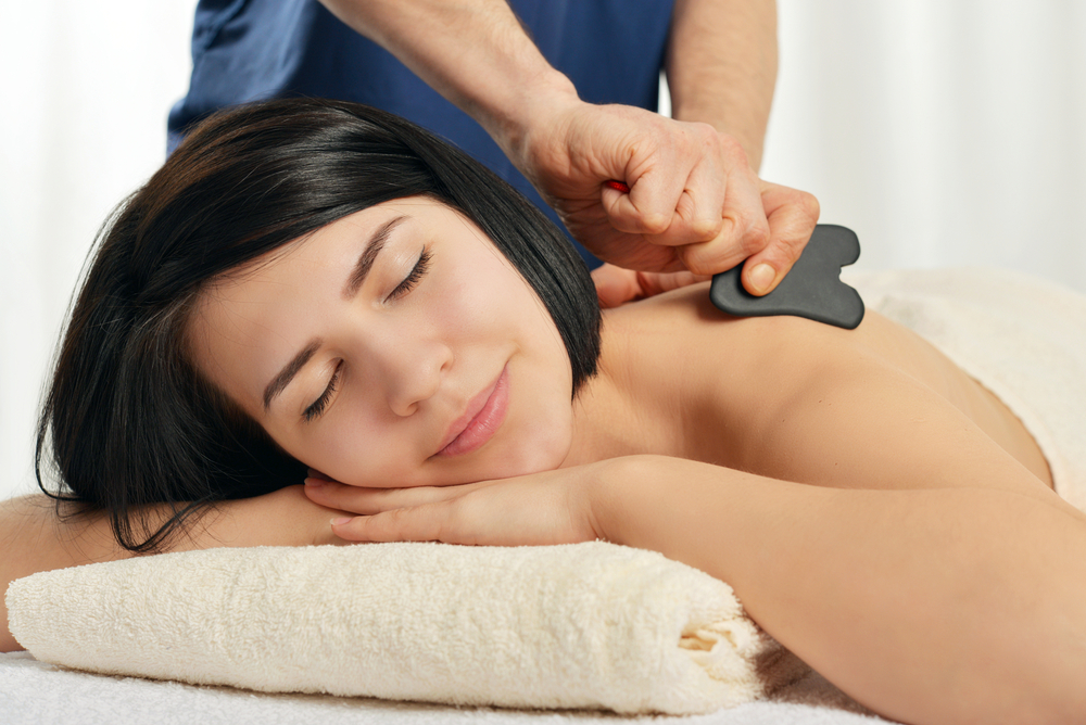 practitioner using gua sha tool on patient's shoulder