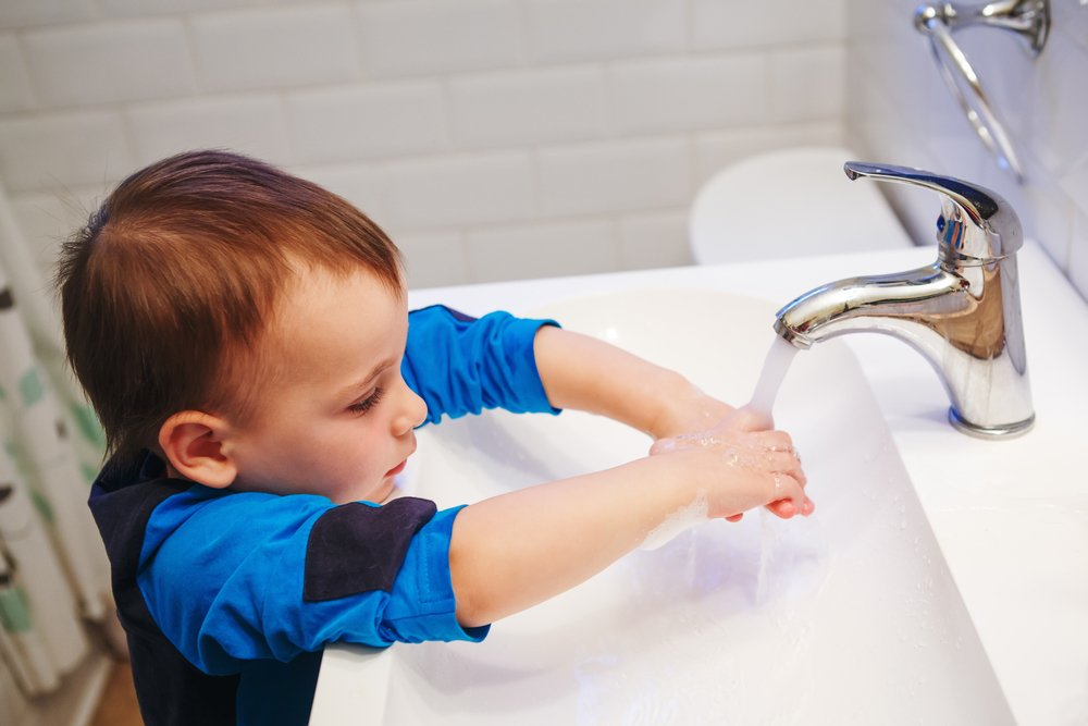 little toddler boy washing his hands in the bathroom