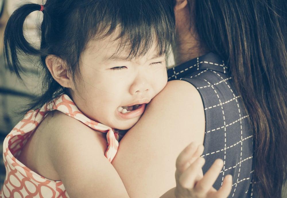 crying toddler girl on her mother's shoulder