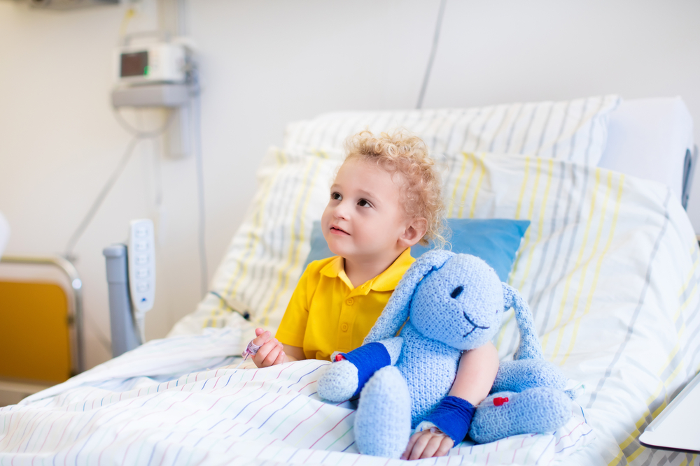 little boy with toy in hospital bed