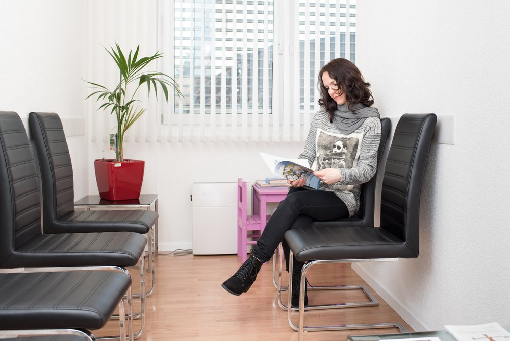 calm woman in doctor's waiting room reading