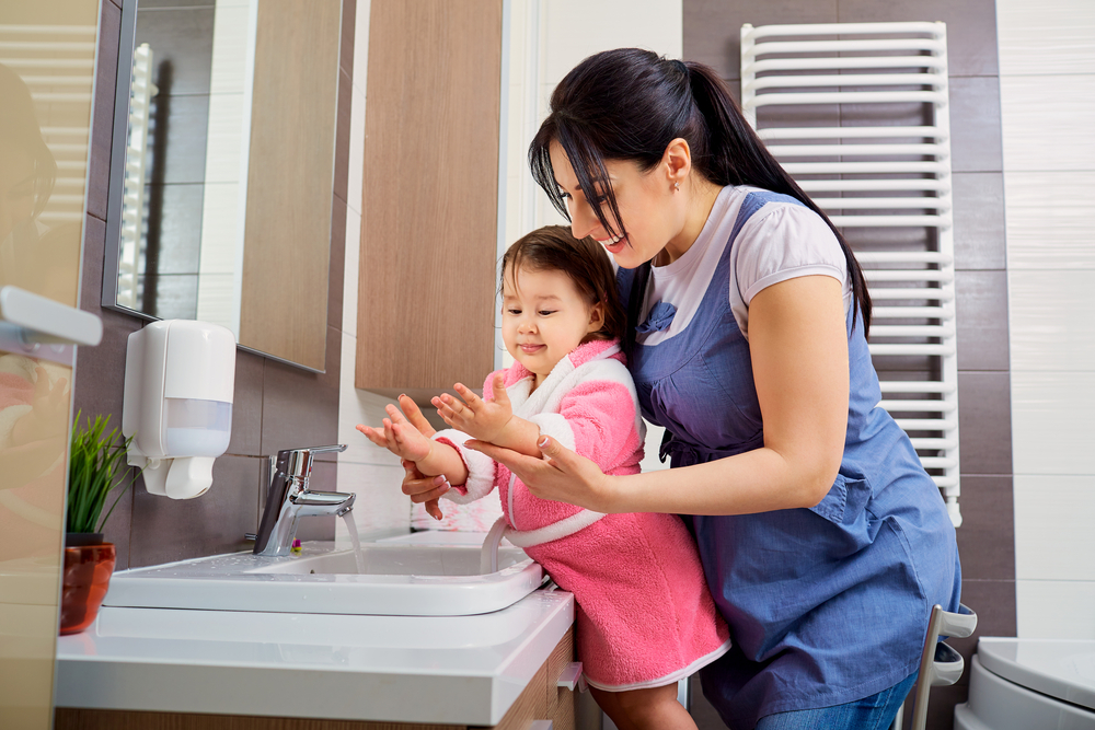 mother helping her toddler wash her hands